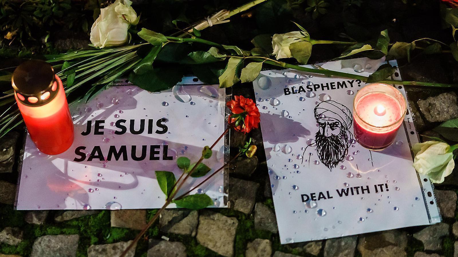 Cartells i espelmes en record de Samuel Paty, el professor decapitat divendres en un atac terrorista als afores de París.