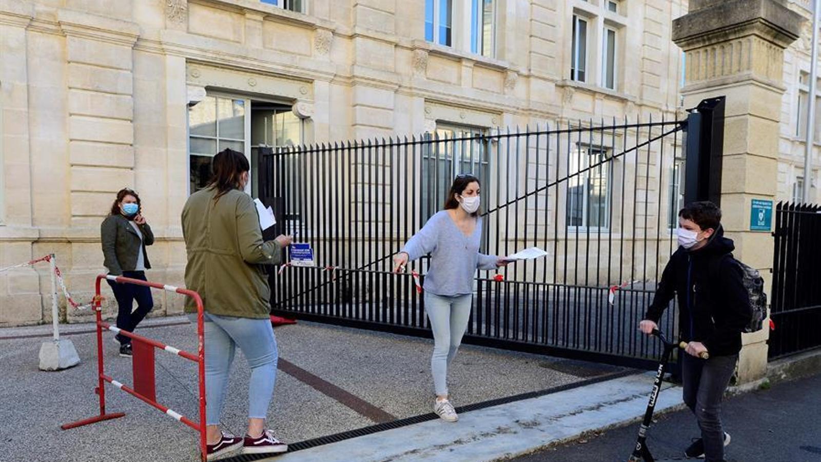 La supervisora d'una escola de Bordeus donant indicacions a un alumne, a la porta del centre en el primer dia de reinici del curs escolar