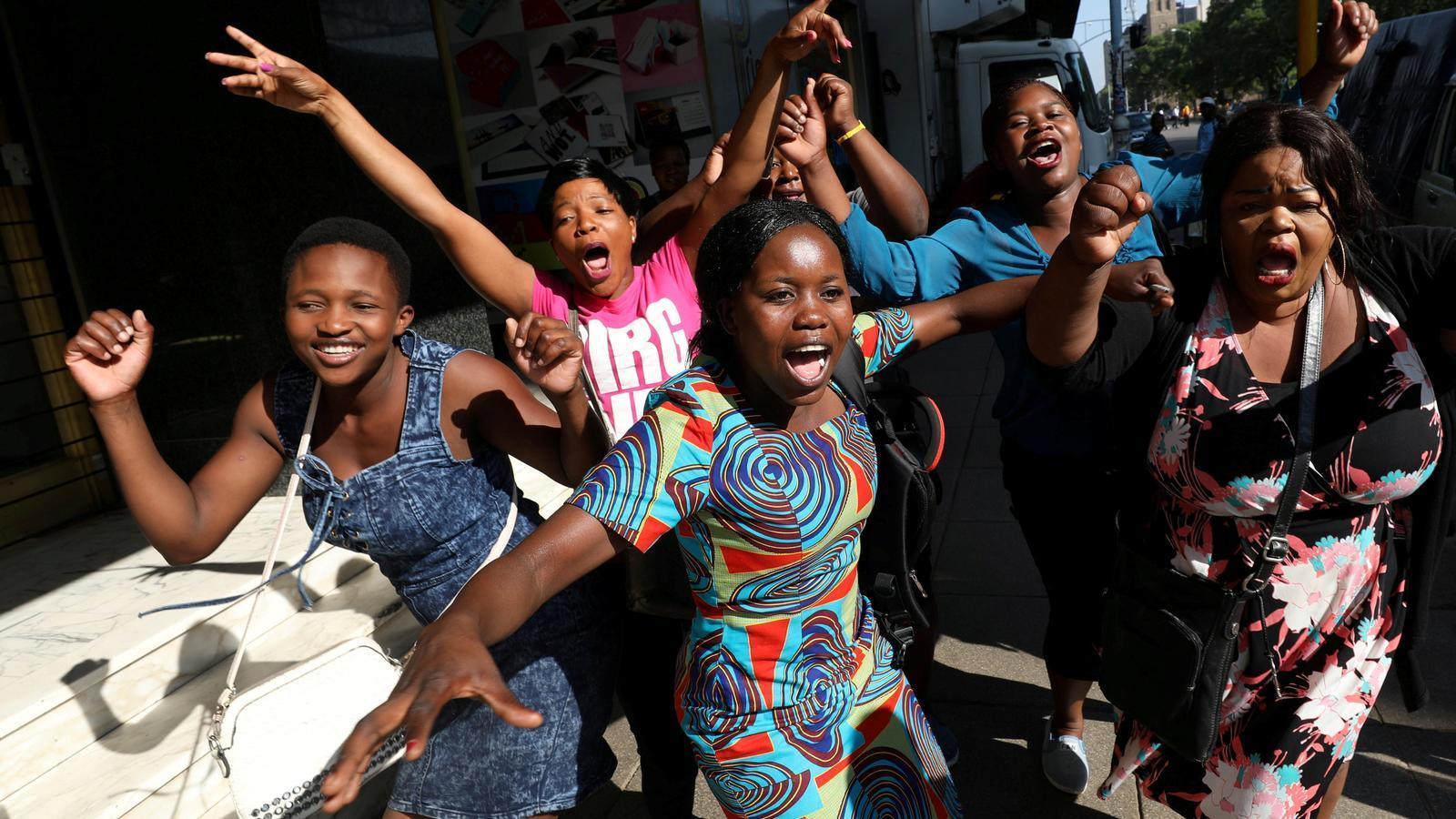Diverses dones celebren la dimissió del ja expresident Robert Mugabe als carrers de Harare, la capital del país