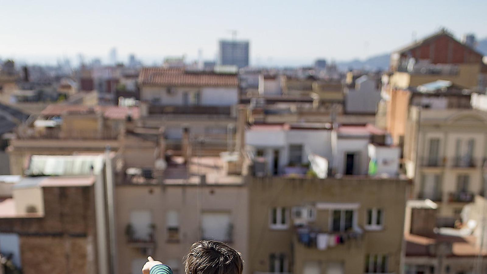 Un nen mirant la ciutat des del terrat de casa.