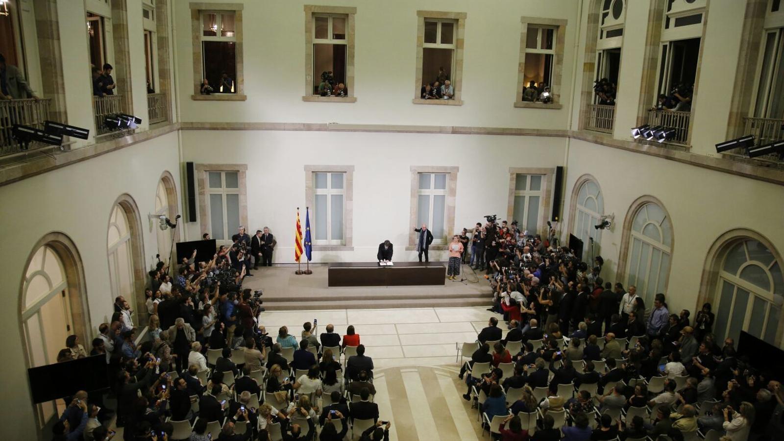 Carles Puigdemont signant la declaració d'independència a l'auditori del Parlament / CRISTINA CALDERER