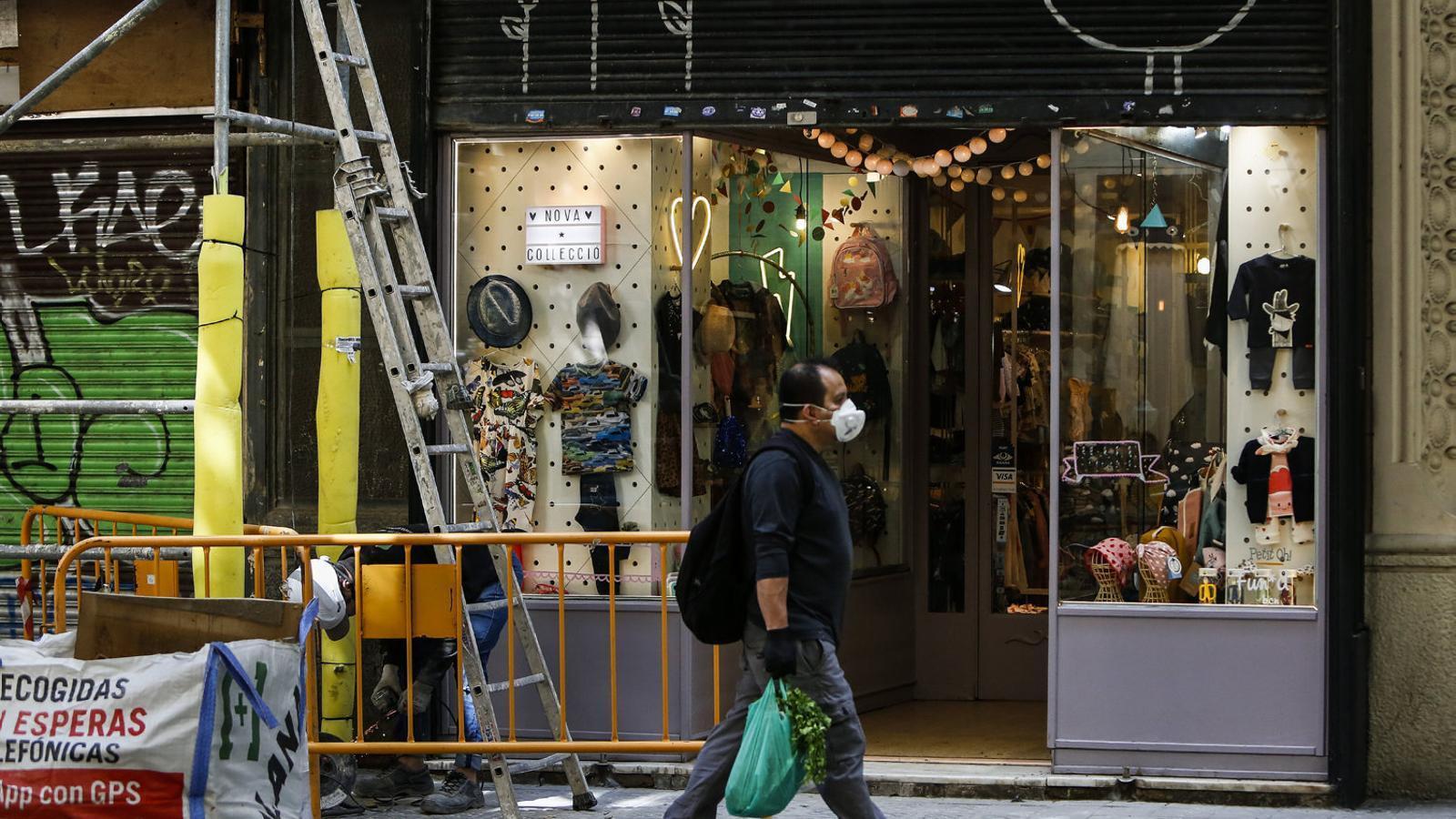 Un home passant ahir per davant d'una botiga al barri de Sant Antoni de Barcelona.