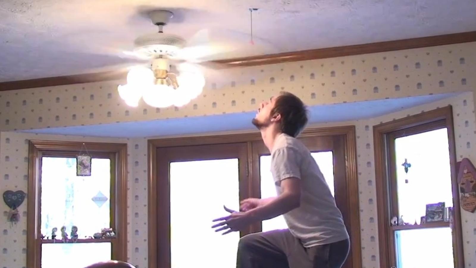 Un jove intenta esquivar les aspes d'un ventilador per caçar un tomàquet que penja del sostre