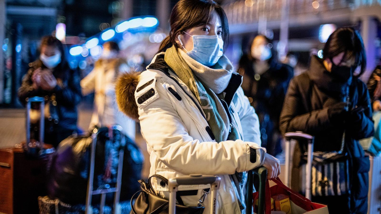 Passatgers, amb màscara protectora, a la seva arribada a l'estació de ferrocarril de Pequín