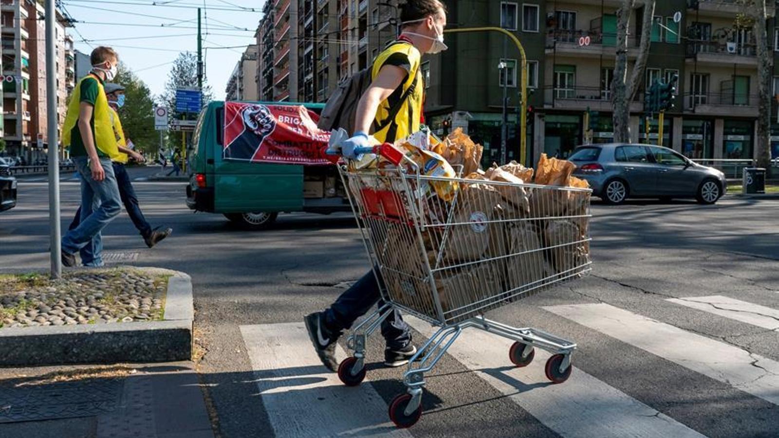 Voluntaris de la Brigada de Milà portant productes de primeres necessitats a les famílies que s'han quedat sense ingressos