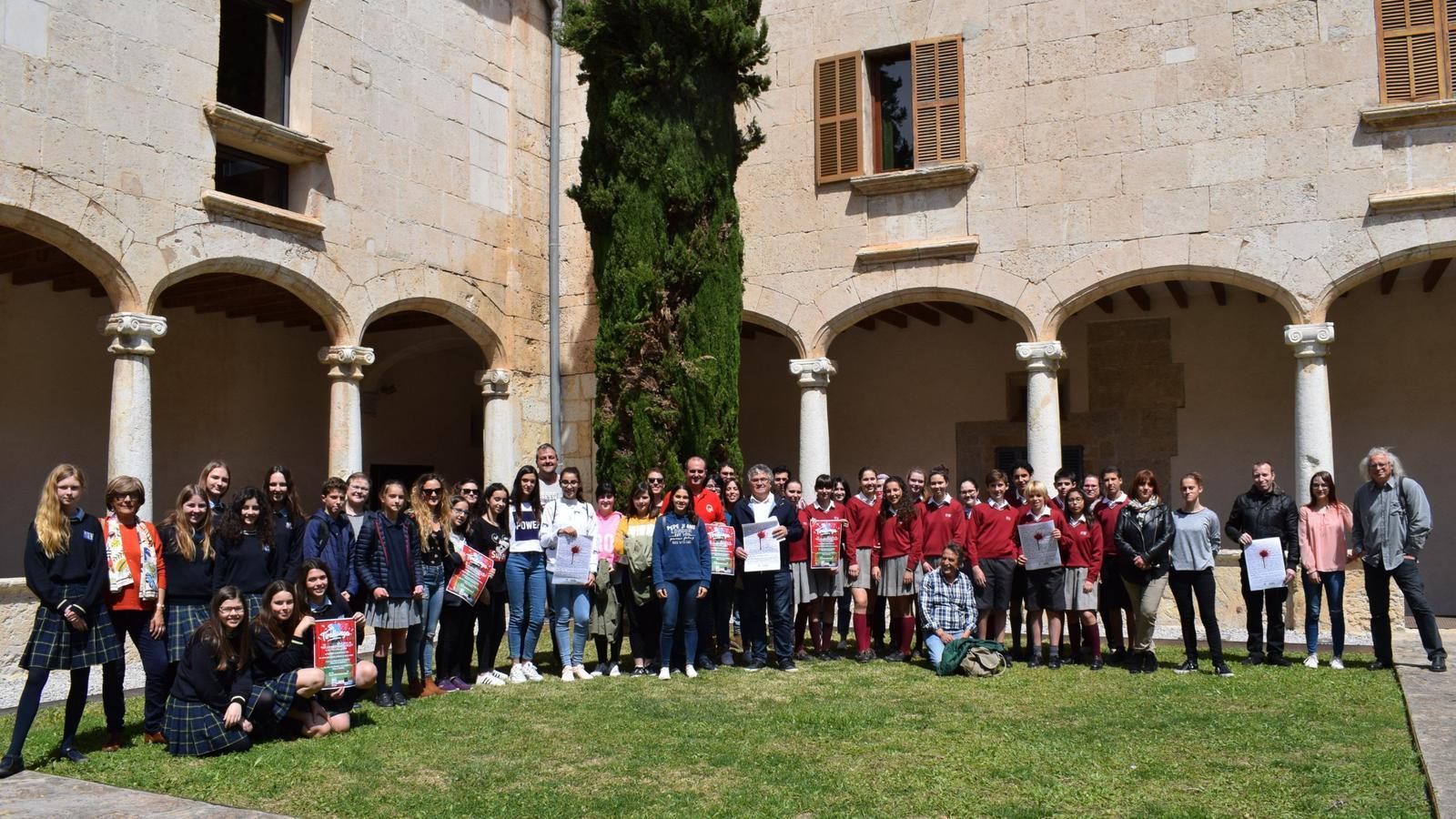 Grups d'escolars amb el cartell dels actes de la Festa del Llibre.