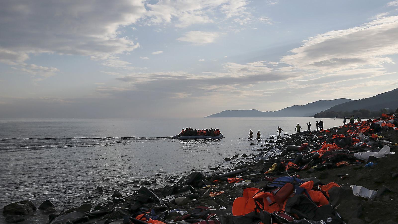 Un grup de refugiats arribant a l'illa de Lesbos en una costa plena d'armilles salvavides, el 2015.