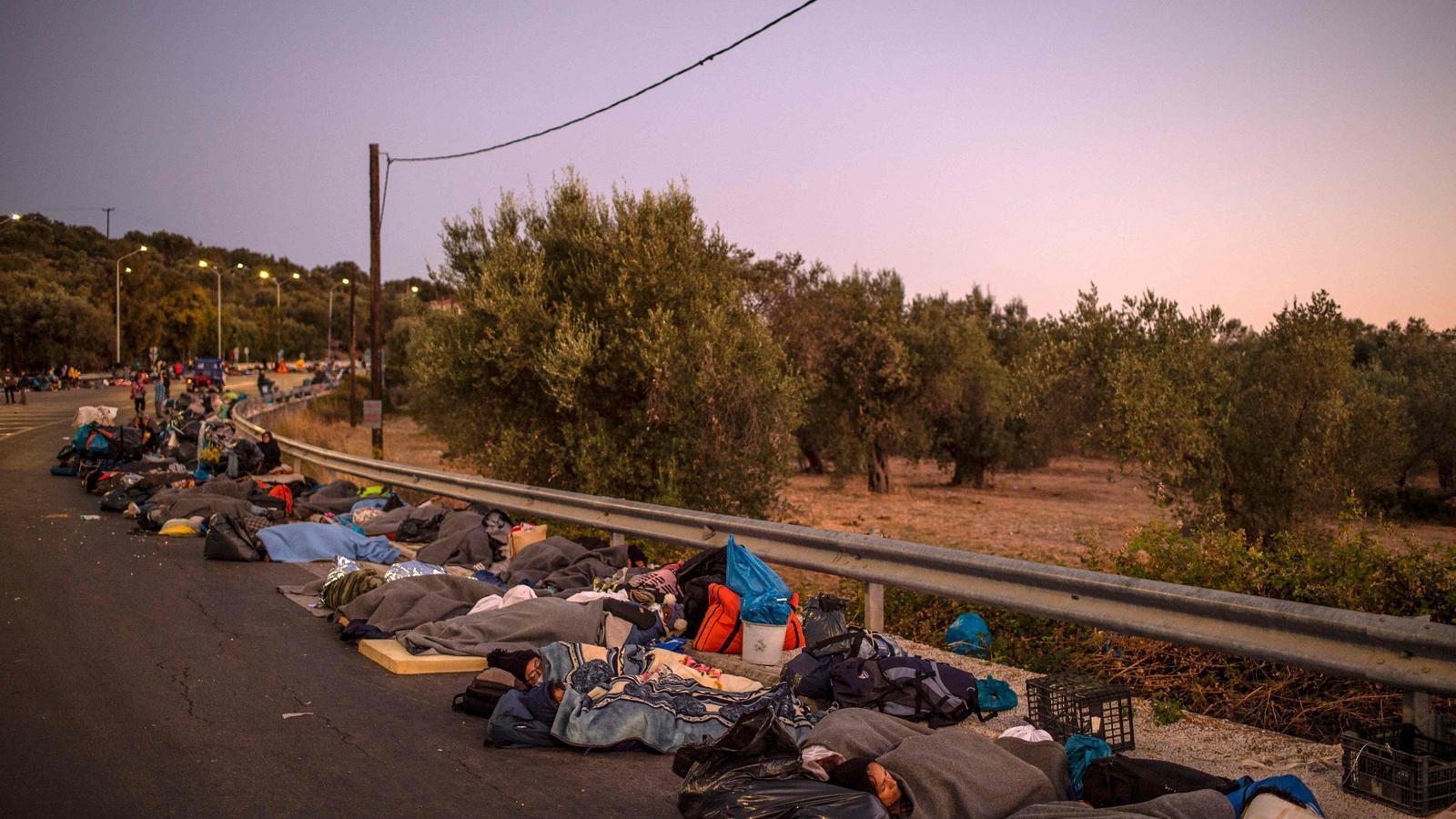 Milers de persones que habitaven el camp de Mória dormint sobre l'asfalt d'una de les carreteres del voltant