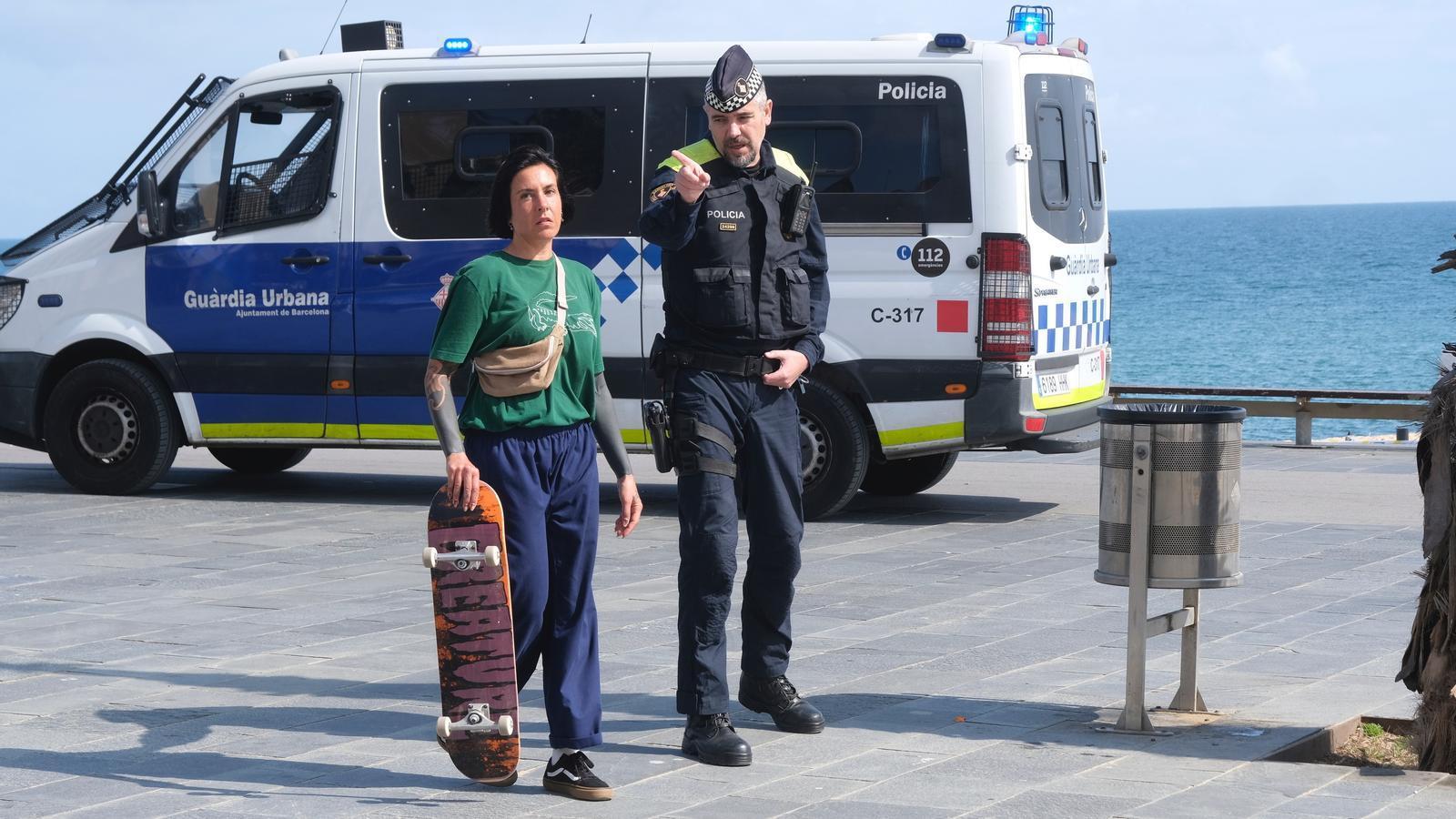 Un agent de la Guardia Urbana dona indicacions a una transeunt per confinar-se a casa