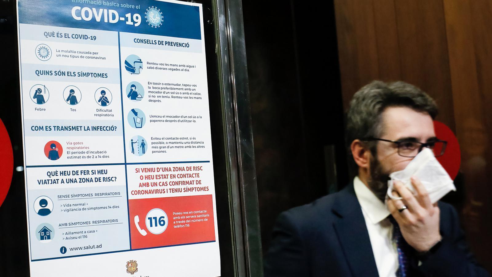 El ministre portaveu, Eric Jover, passa davant d'un dels cartells amb recomanacions sobre la Covid-19. / SFG