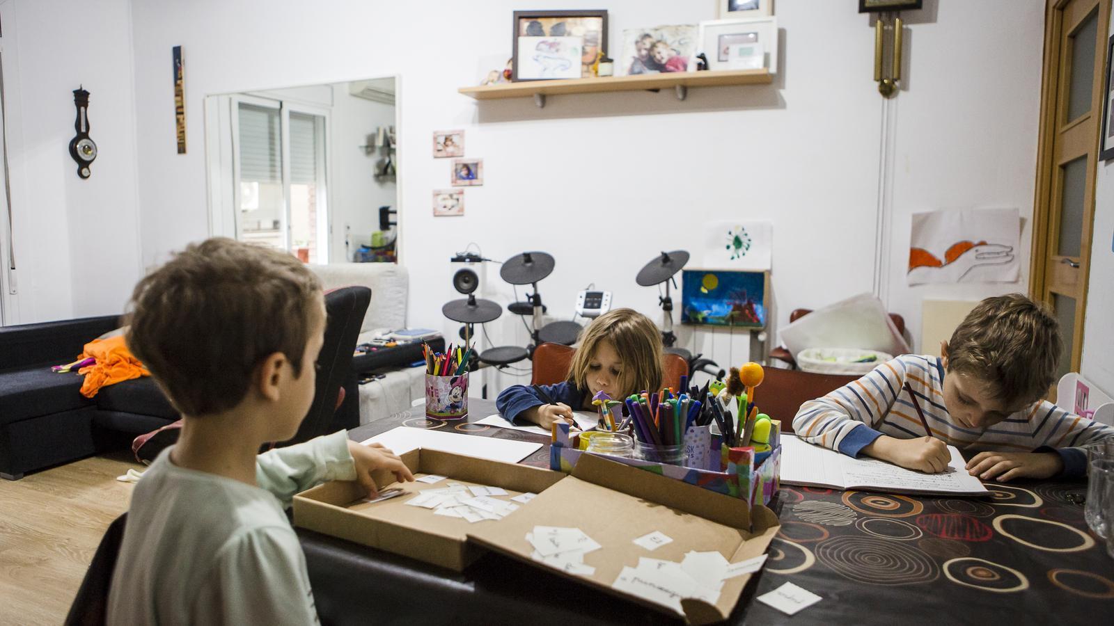 Uns nens de 5, 7 i 8 anys fent deures a casa
