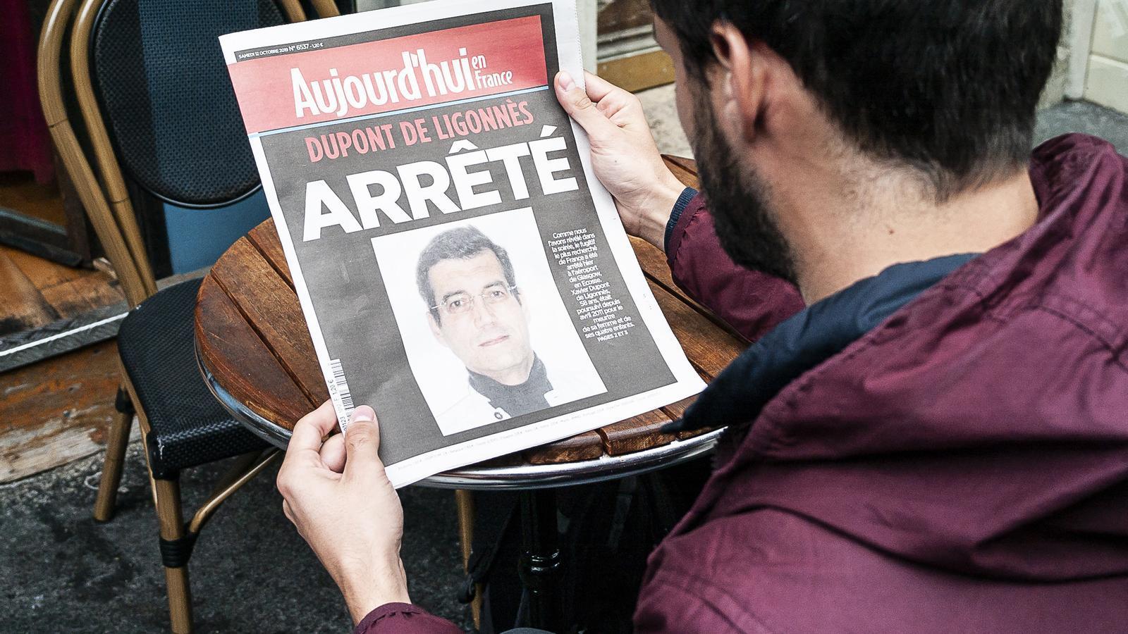 Un jove observant la portada de 'Le Parisien' amb una fotografia de Dupont