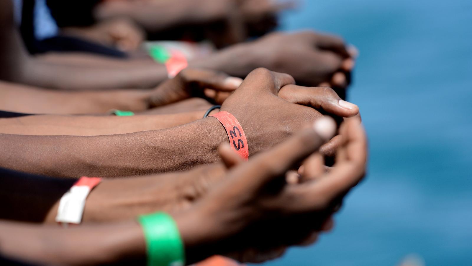 Les mans de diversos migrants a bord de l''Aquarius'.