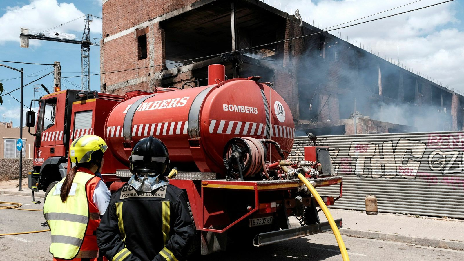 Bombers treballant en les tasques d'extinció de l'incendi d'un edifici ocupat a Eivissa.