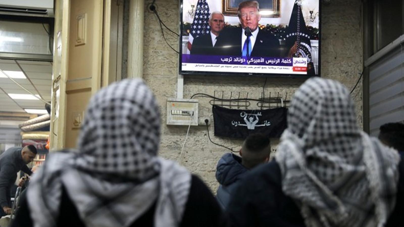 Dos palestins segueixen la compareixença de Trump en què anuncia el reconeixement de Jerusalem com a capital d'Israel.