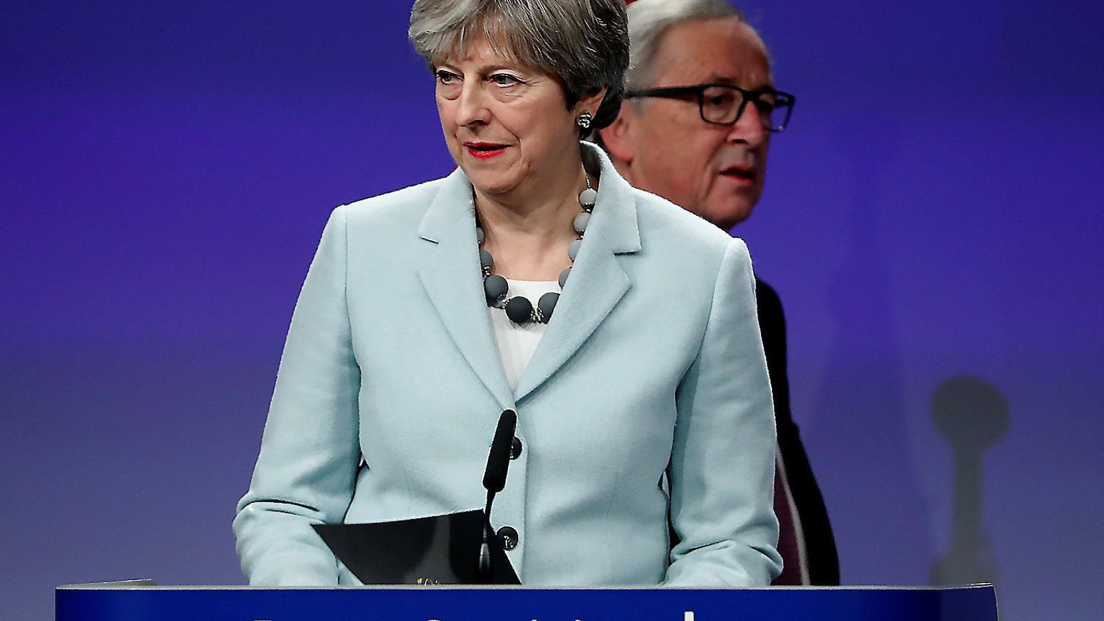 Theresa May i Jean-Claude Juncker ahir a Brussel·les.   A sota, una imatge d'Arlene Foster, líder del Partit Democràtic Unionista d'Irlanda del Nord.