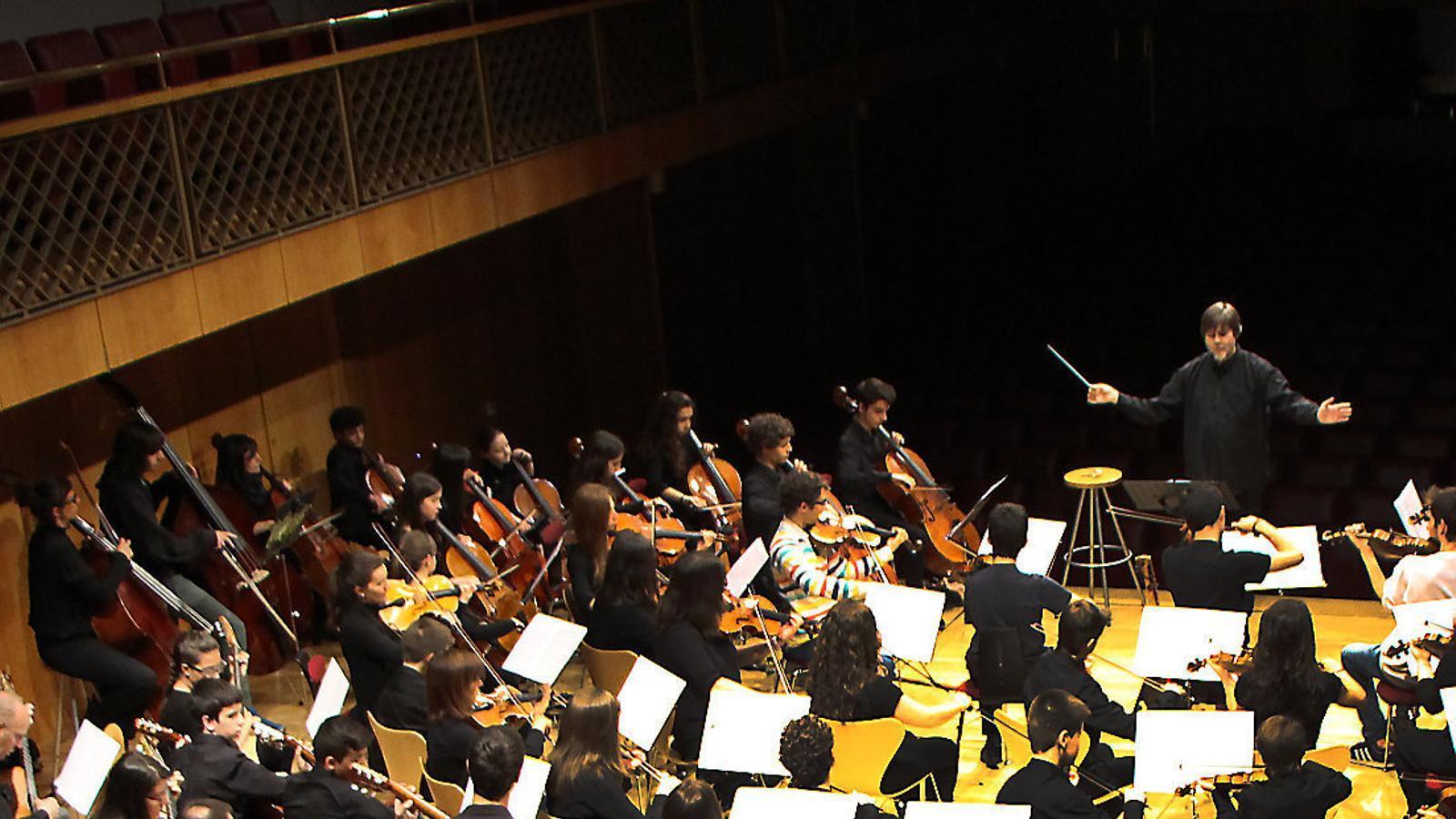 Alumnes d'escoles de música del país amb els músics de la JONCA durant un concert.