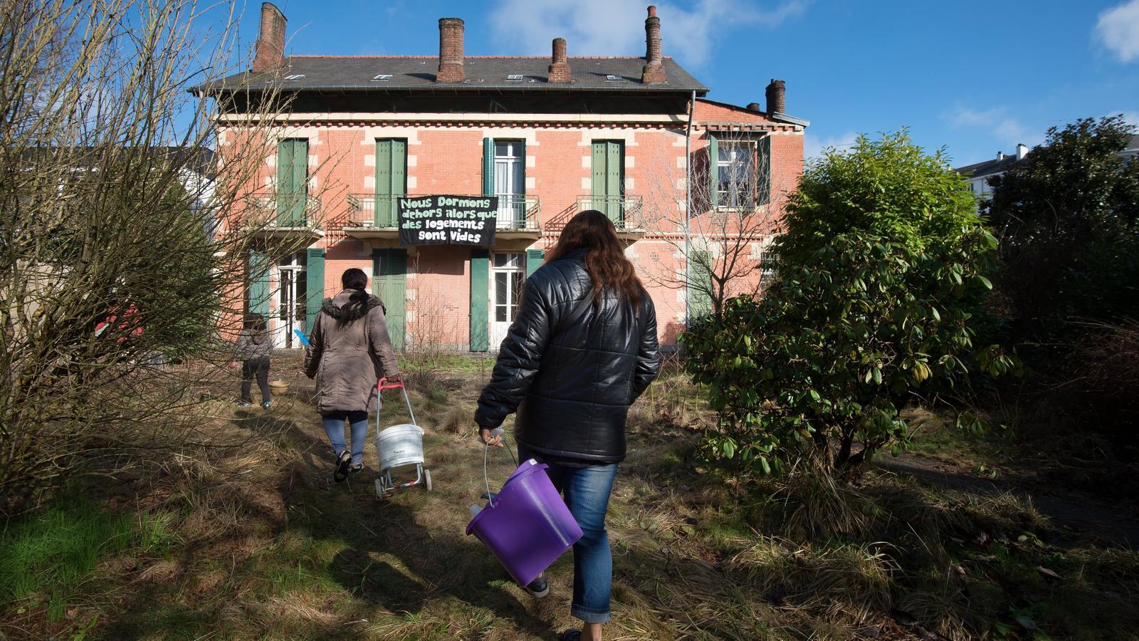 """Un grup de dones migrants viuen en una casa, abandona a Rennes, França, a la façana de la qual penja una pancarta que diu """"dormim fora mentre les cases estan buides"""""""