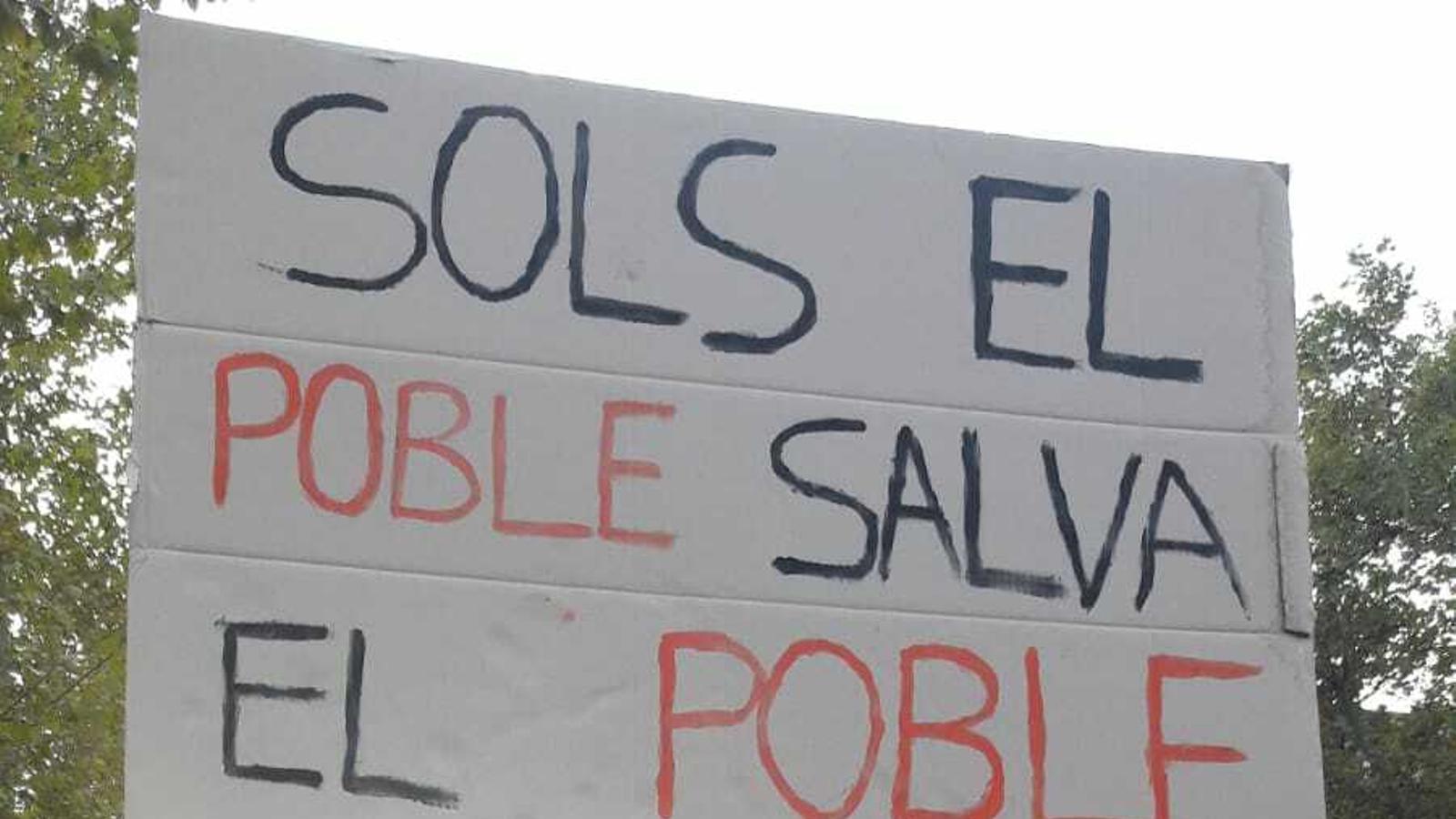 """Un noi sosté una pancarta en la qual es pot llegir  """"Sols el poble salva el poble"""" ahir durant la mobilització durant la vaga general"""