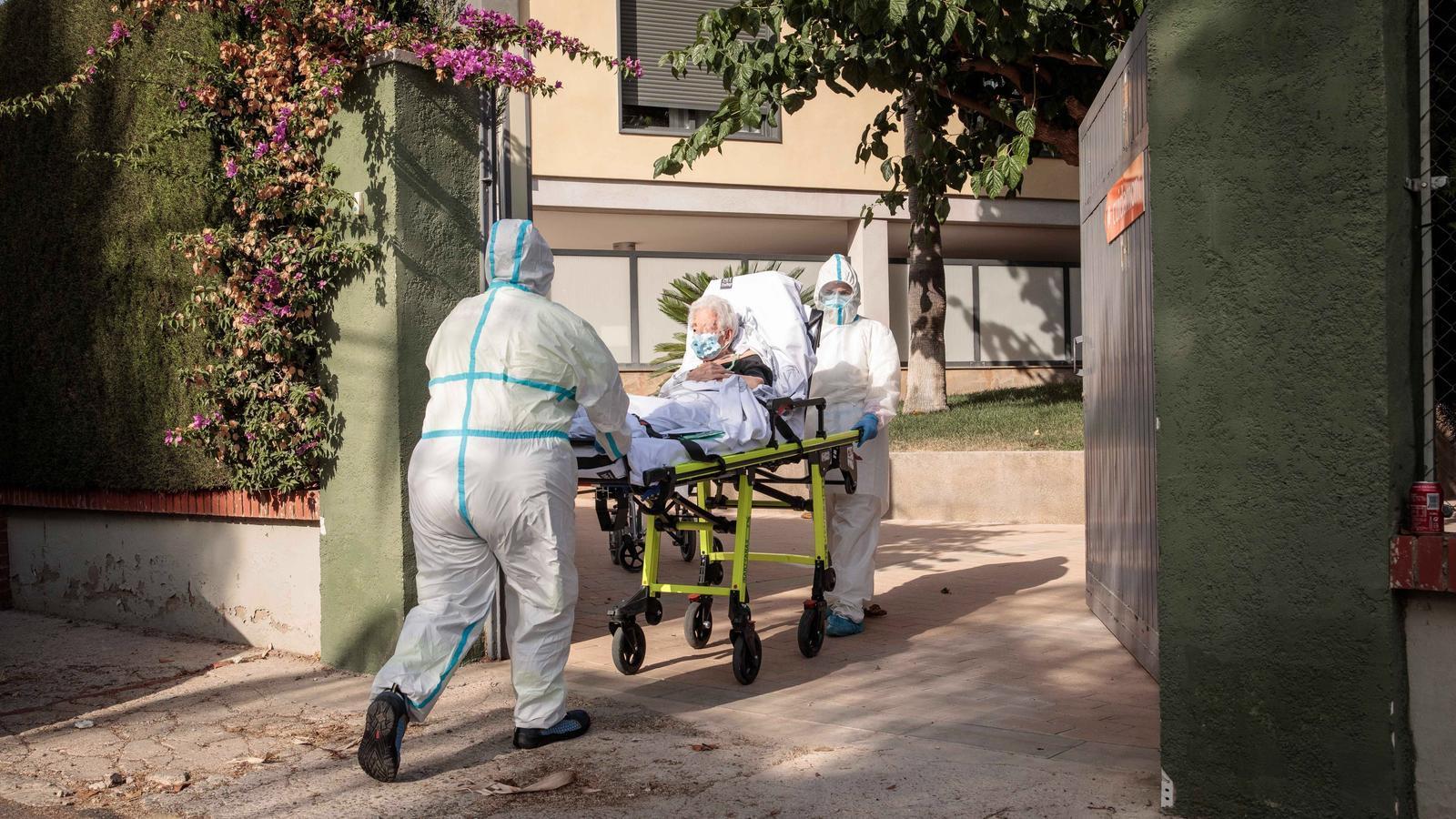 Dos treballadors sanitaris transporten una dona major a la residència de l'Eliana, on s'ha detectat un brot de coronavirus