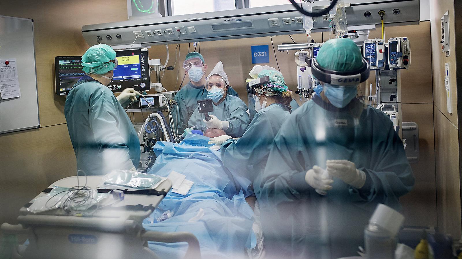 Infermeres i metges d'una de les UCI de l'Hospital de la Vall d'Hebron atenent un pacient greu de covid-19.