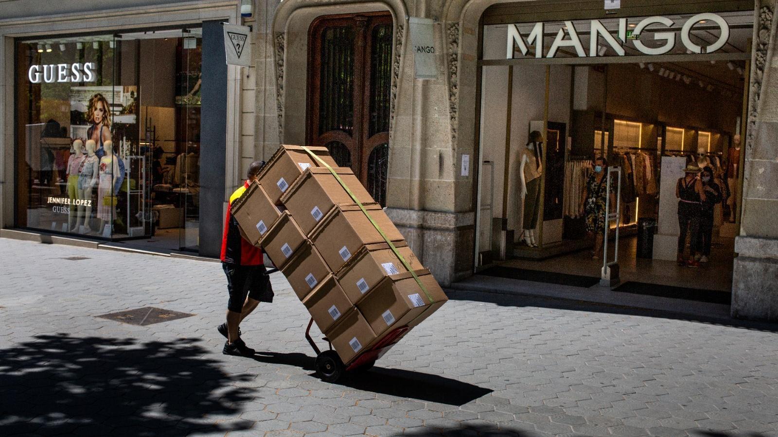 Un treballador transporta caixes de roba al passeig de Gràcia de Barcelona.