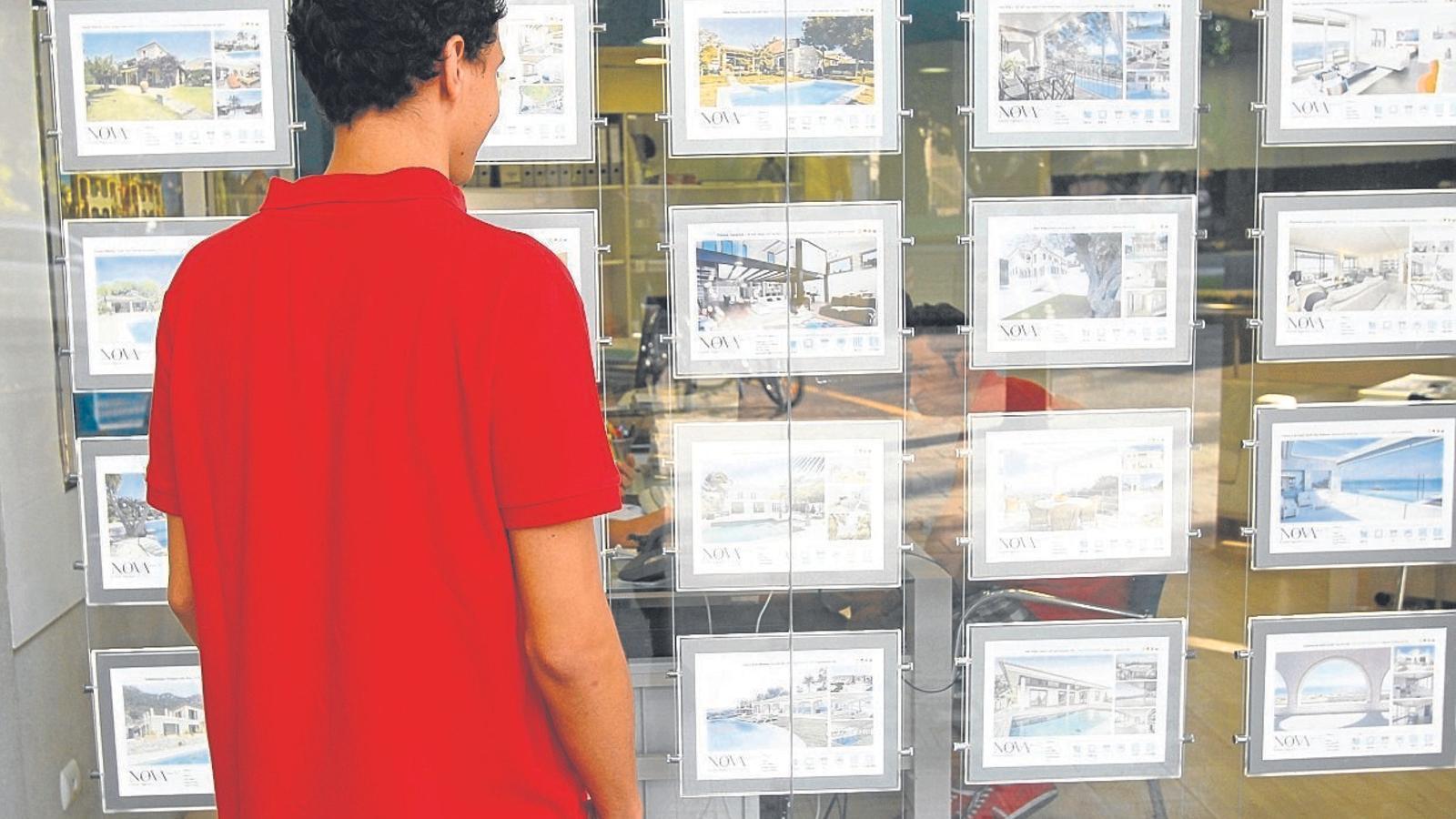 Un jove mira anuncis d'habitatges de lloguer