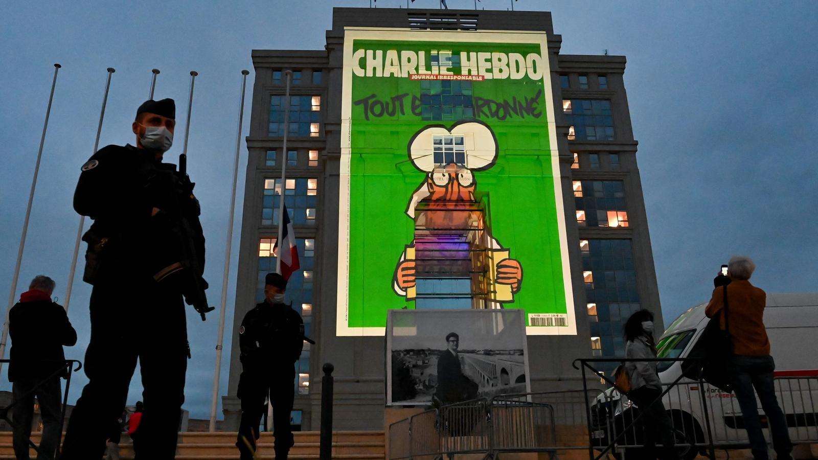 Policies davant la seu del govern regional de Montpeller, amb la caricatura projectada.