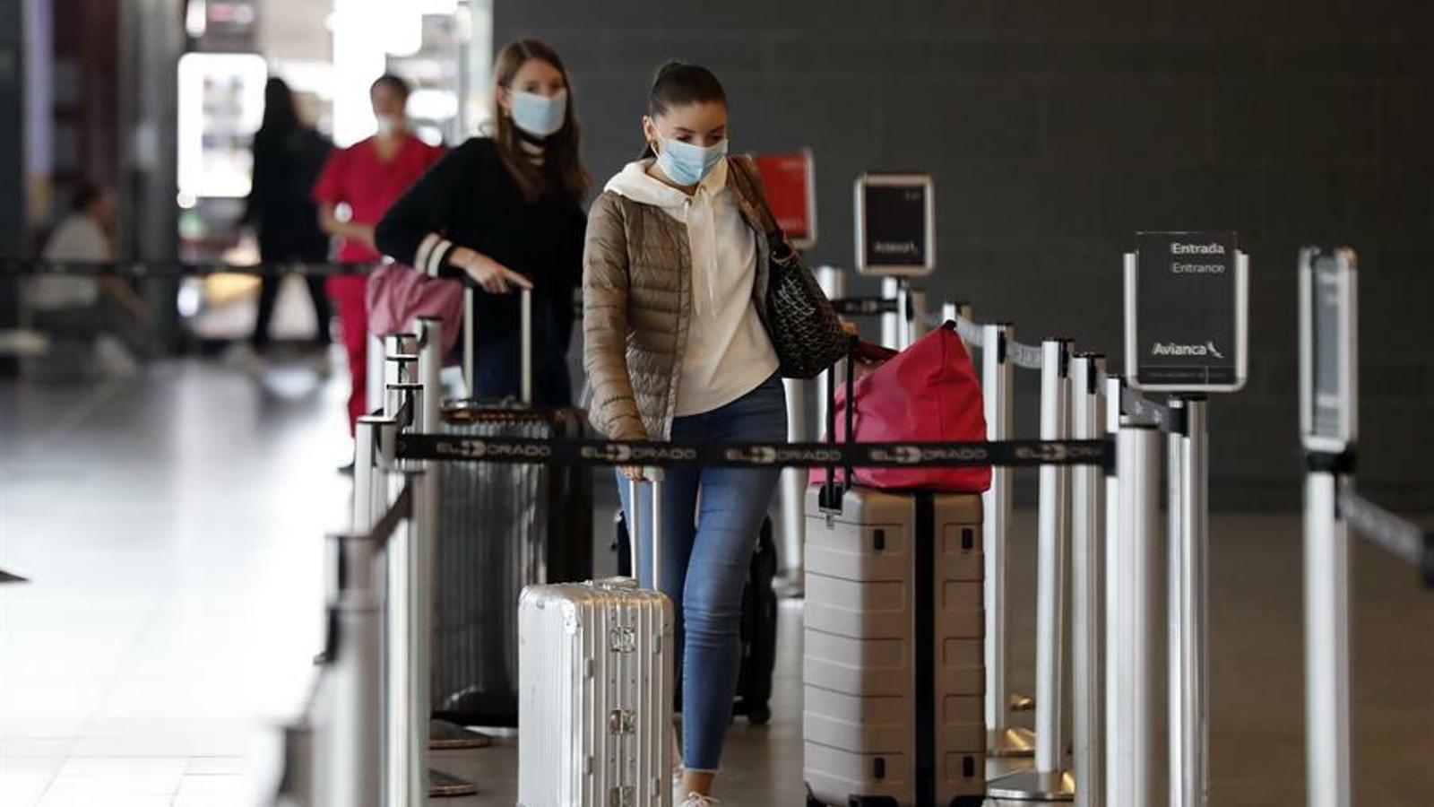 Unes turistes protegides amb mascareta i carregades amb maletes, a l'aeroport del Dorado de Colòmbia