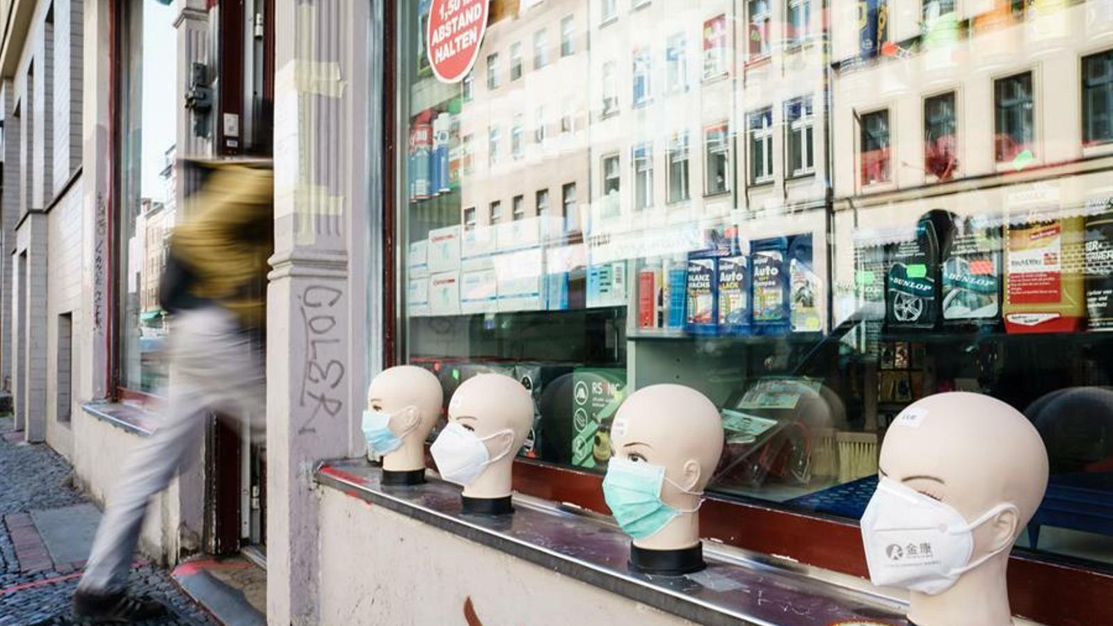 Mascaretes de protecció en venda en l'aparador exterior d'una botiga de Berlín