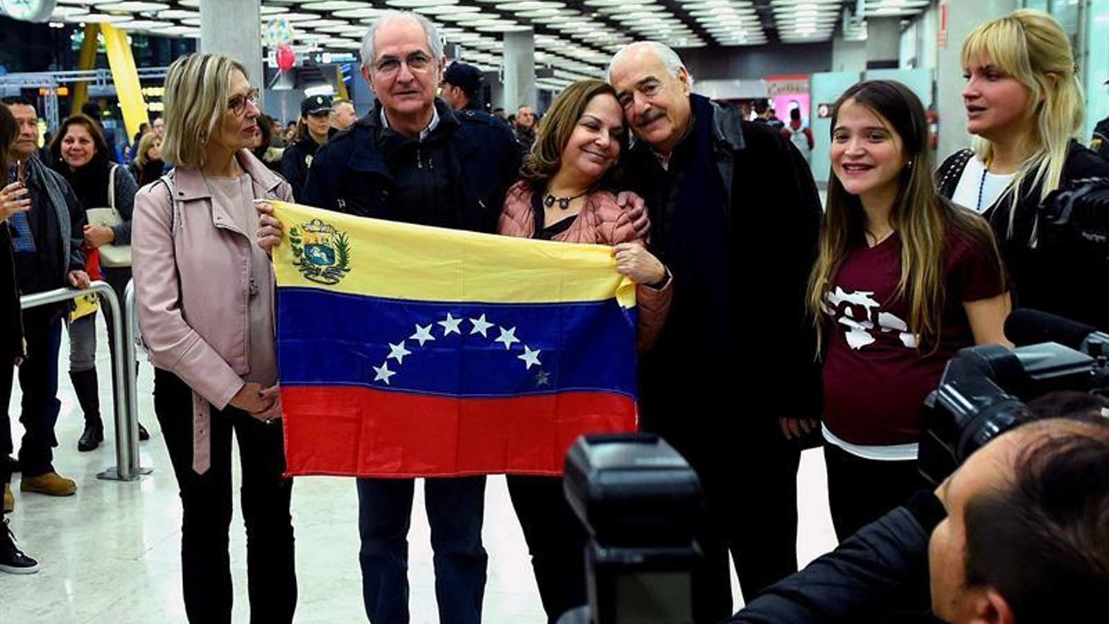 Antonio Ledezma subjecta la bandera veneçolana, acompanyat de la seva família i l'expresident Pastrana, a la seva arribada a l'aeroport de Madrid.