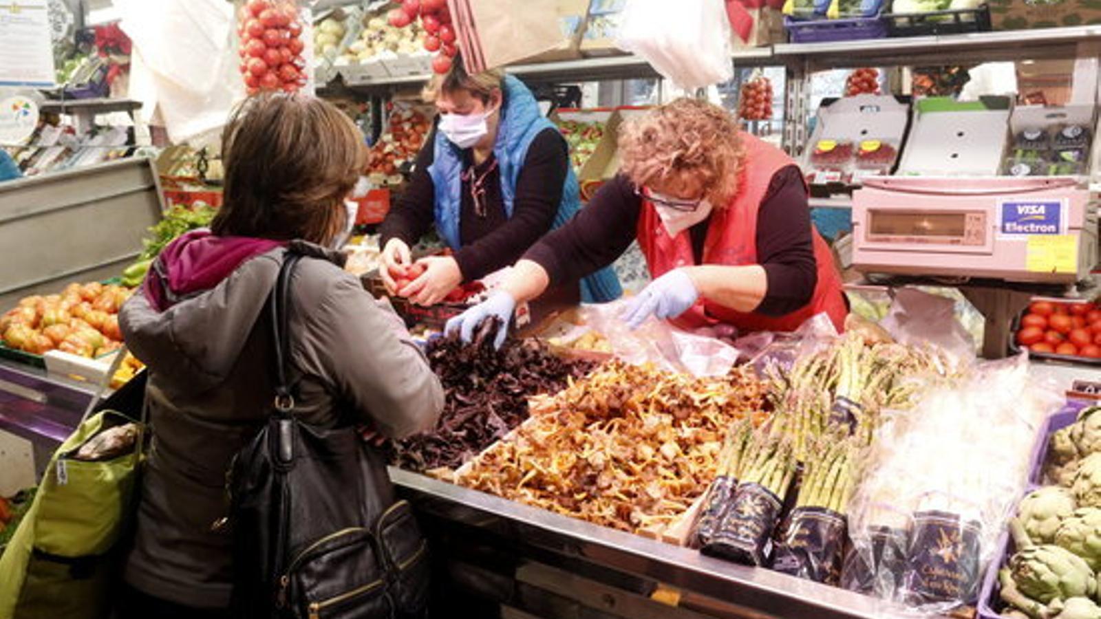 Una dependenta despatxa bolets a una clienta del mercat del Lleó de Girona