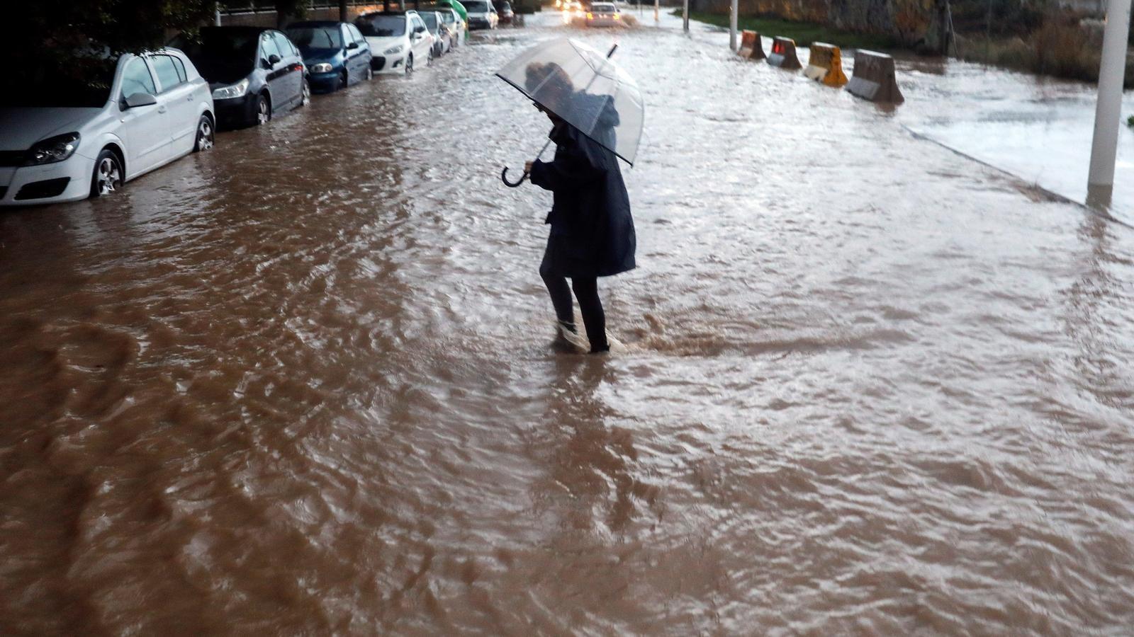 Una dona creu un carrer de València inundat per les fortes pluges registrades aquest divendres