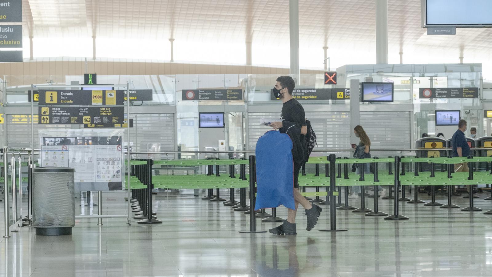 Un passatger amb mascareta a l'aeroport del Prat, a Barcelona