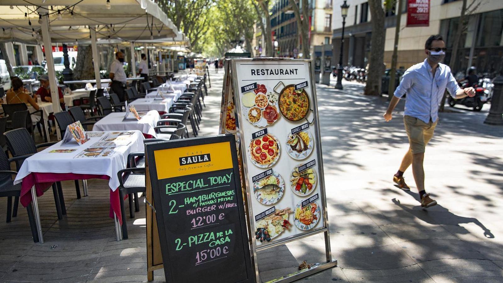 Terrasses pràcticament buides un migdia a la Rambla de Barcelona, malgrat les ofertes i la presència dels cambrers esperant per oferir el menú.