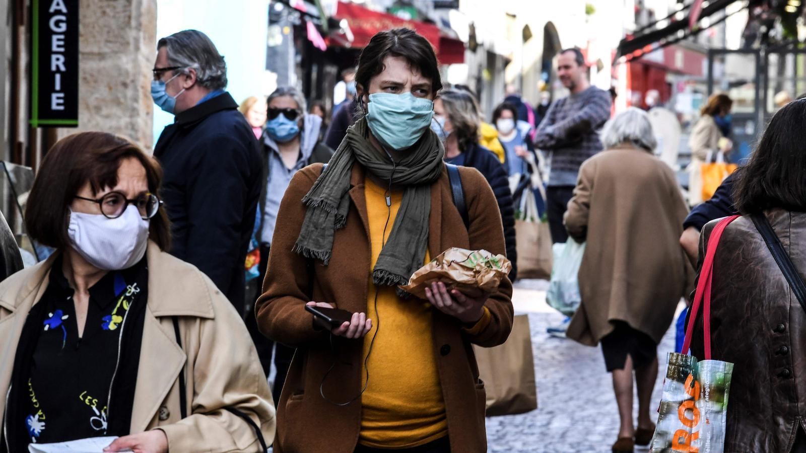 Persones passegen amb mascareta pel carrer a París