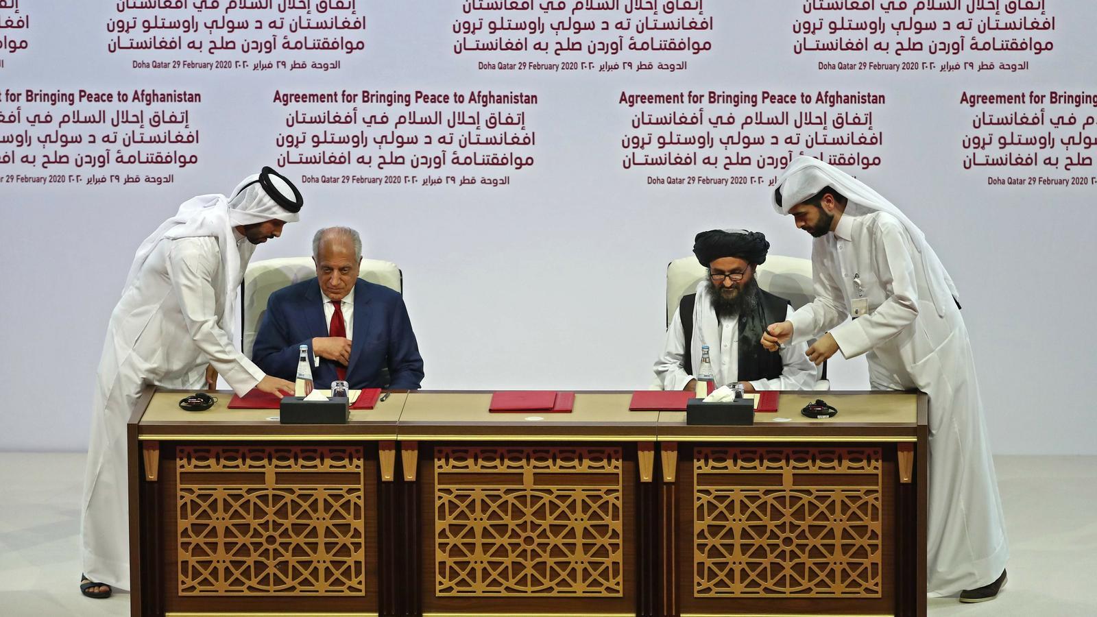 El mul·là Abdul Ghani i el Baradar i el representant del govern afganès, Zalmai Khalilzad, firmen l'acord a Doha.