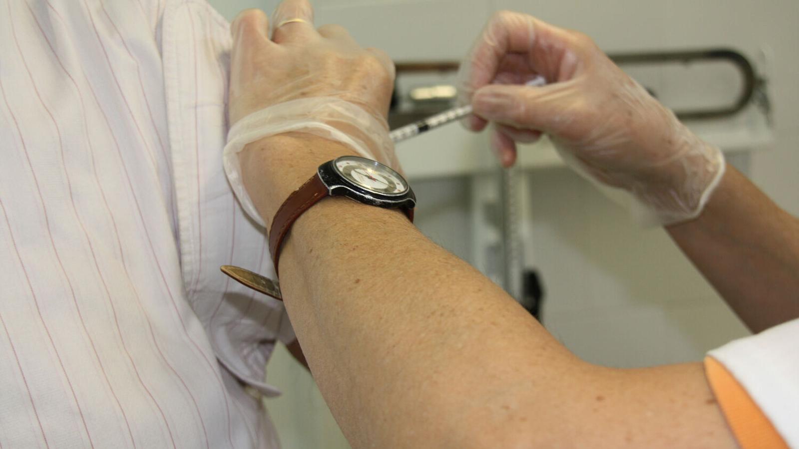 Una infermera administra una vacuna de la grip