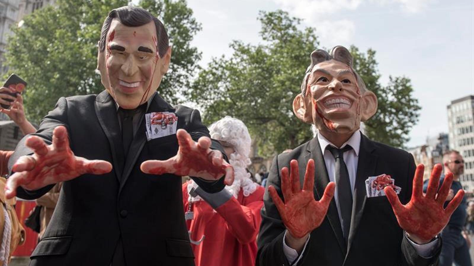 Manifestants amb les caretes de Bush i Blair tacades de sang, avui al barri de Westminster de Londres. / WILL OLIVER / EFE