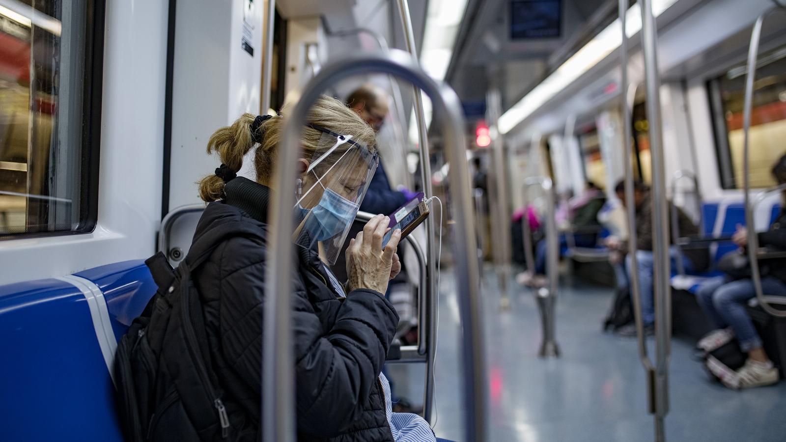 Una dona mira el seu telèfon al metro de Barcelona