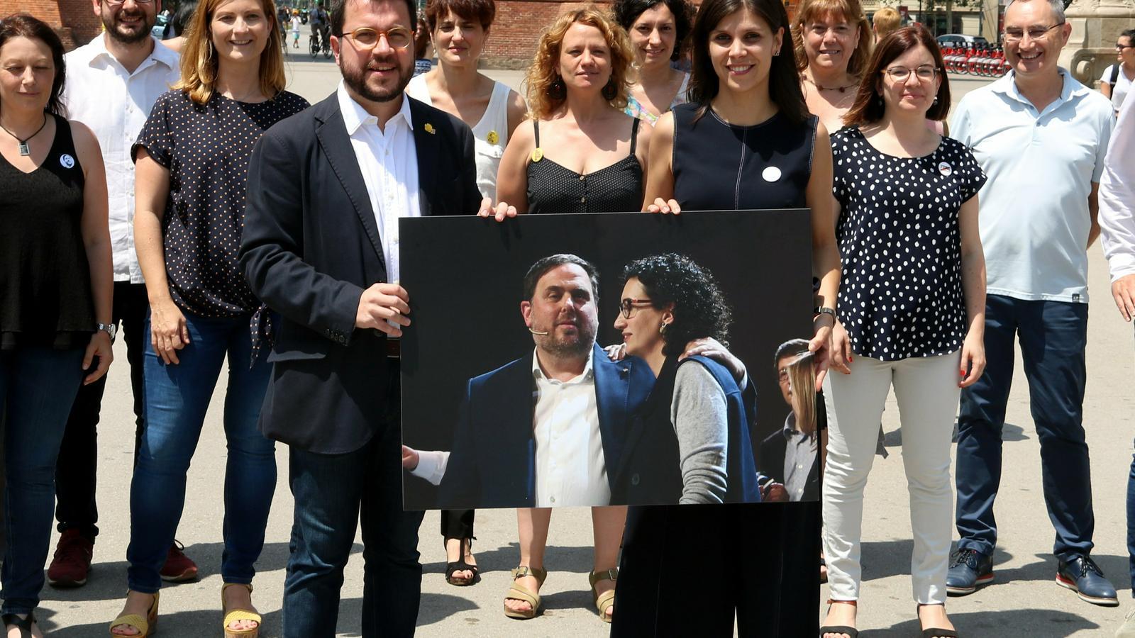 Pere Aragonès i Marta Vilalta amb una foto d'Oriol Junqueras i Marta Rovira en la trobada de la nova candidatura d'ERC.