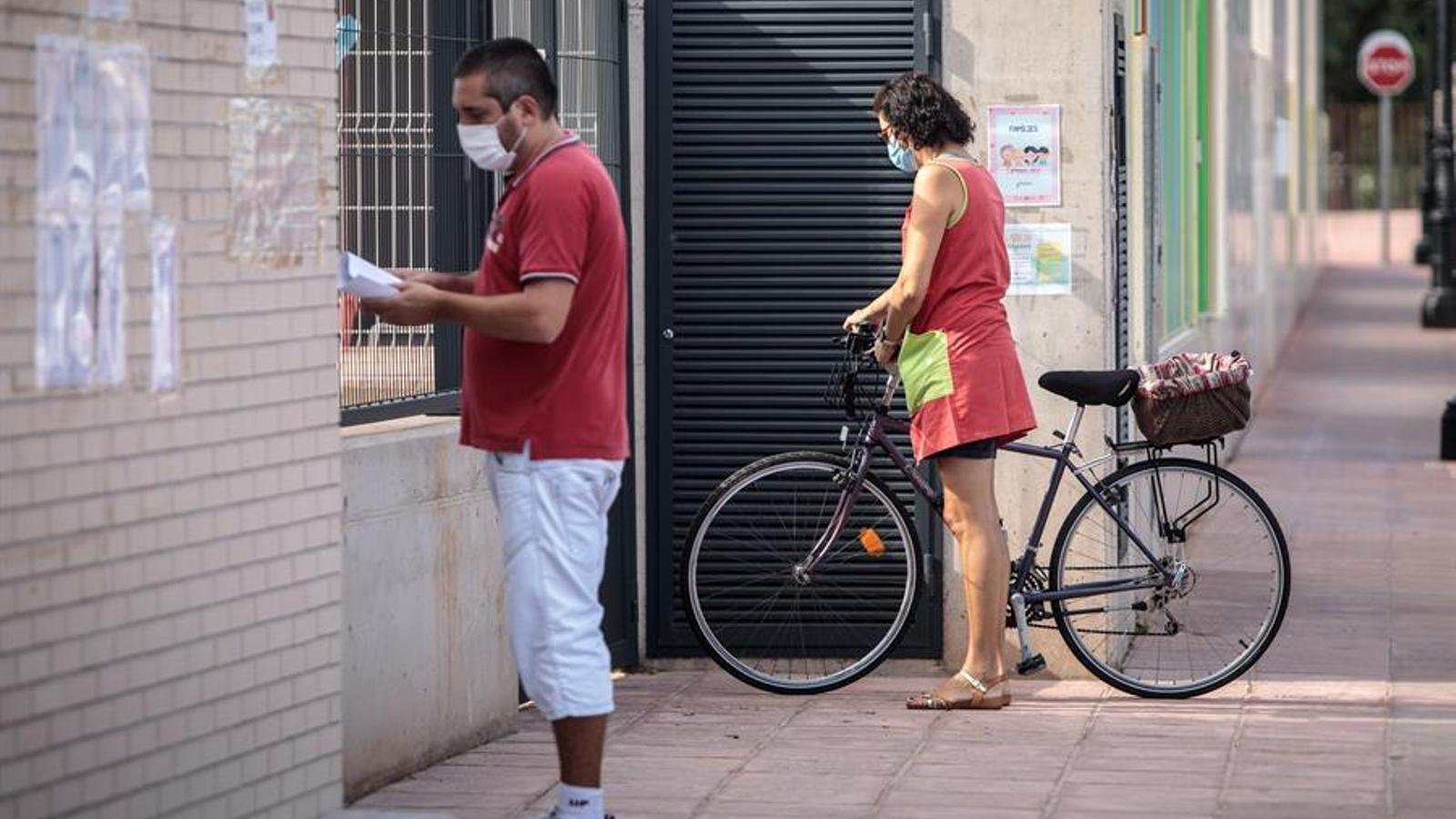 Diverses persones esperen a les portes del col·legi de Primària del CEIP Els Germanells de Rafelbunyol (València), on una vintena d'alumnes ha estat aïllada seguint el protocol sanitari, igual que la seva professora, després del positiu per covid-19 d'una les seves alumnes i aquest dijous estan a l'espera del resultat de les proves PCR fetes a tots. EFE/ Biel Aliño