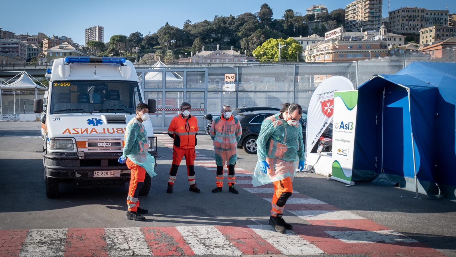 Personal sanitari a punt d'embarcar pacients de coronavirus en un vaixell atracat al port de Gènova