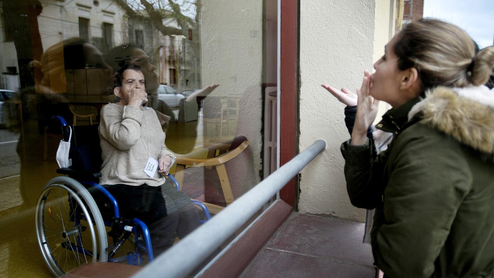 Una familiar enviant un petó a través del vidre de la residència Prat, de Tona, que la setmana passada ja va demanar la intervenció de la Generalitat