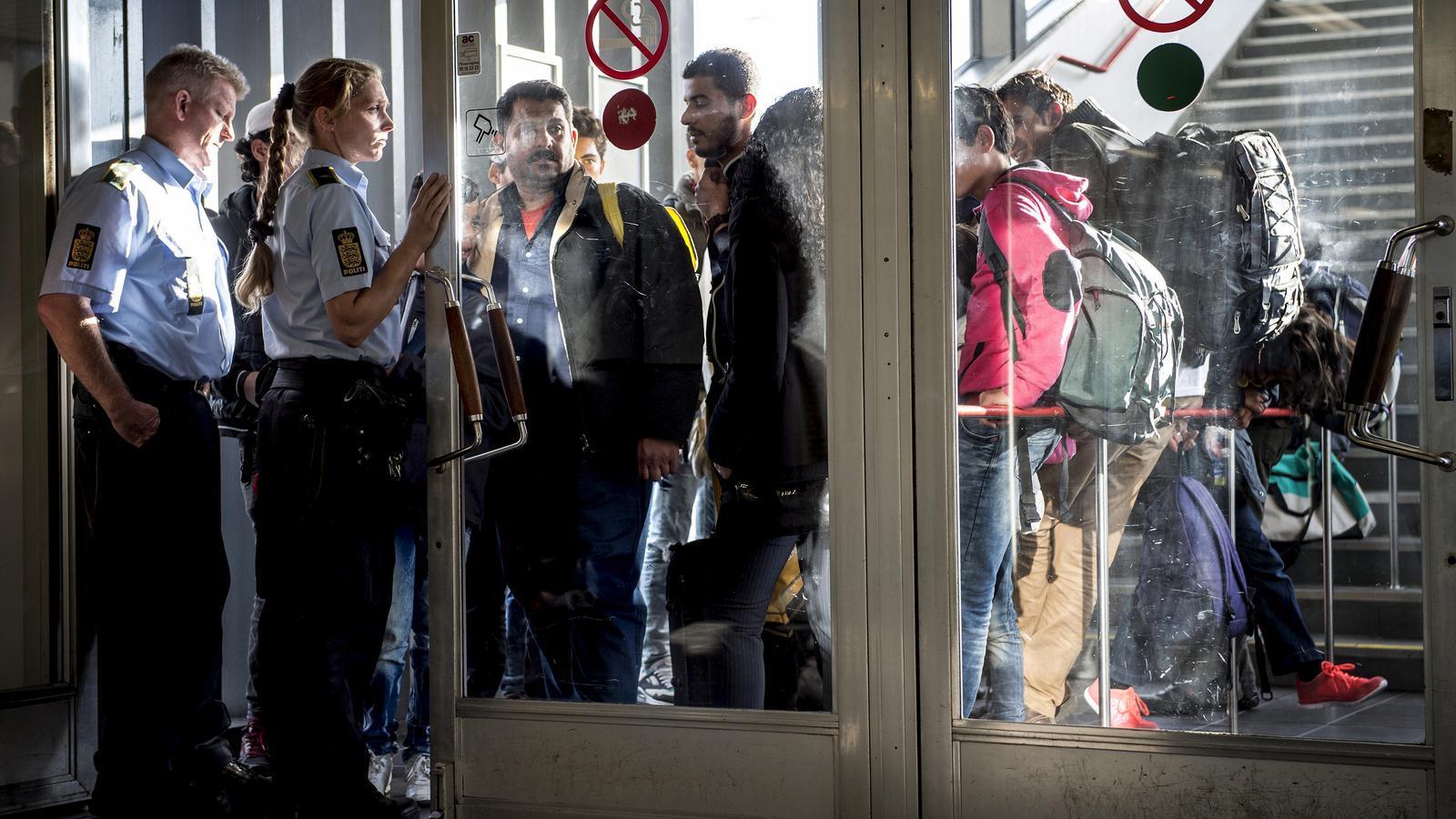 La policia danesa controla l'arribada d'immigrants al país.