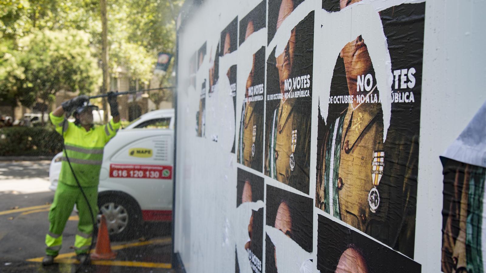 Un operari de l'Ajuntament de Barcelona retira els cartells de la campanya al passeig de Sant Joan / FRANCESC MELCION