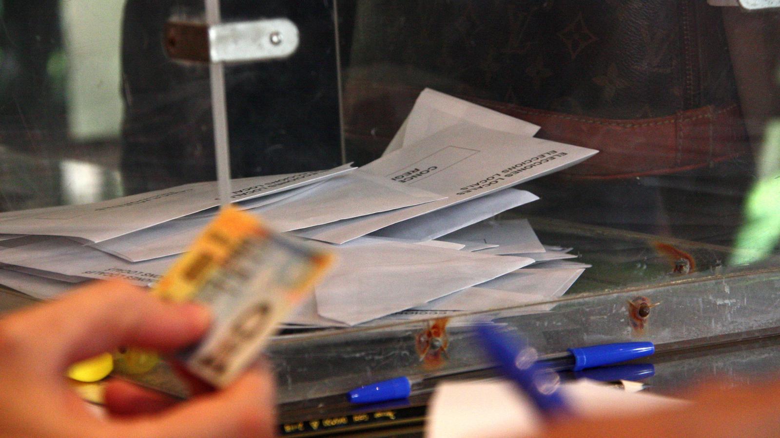 Imatge d'arxiu d'una urna i una mà que comprova el DNI abans de votar