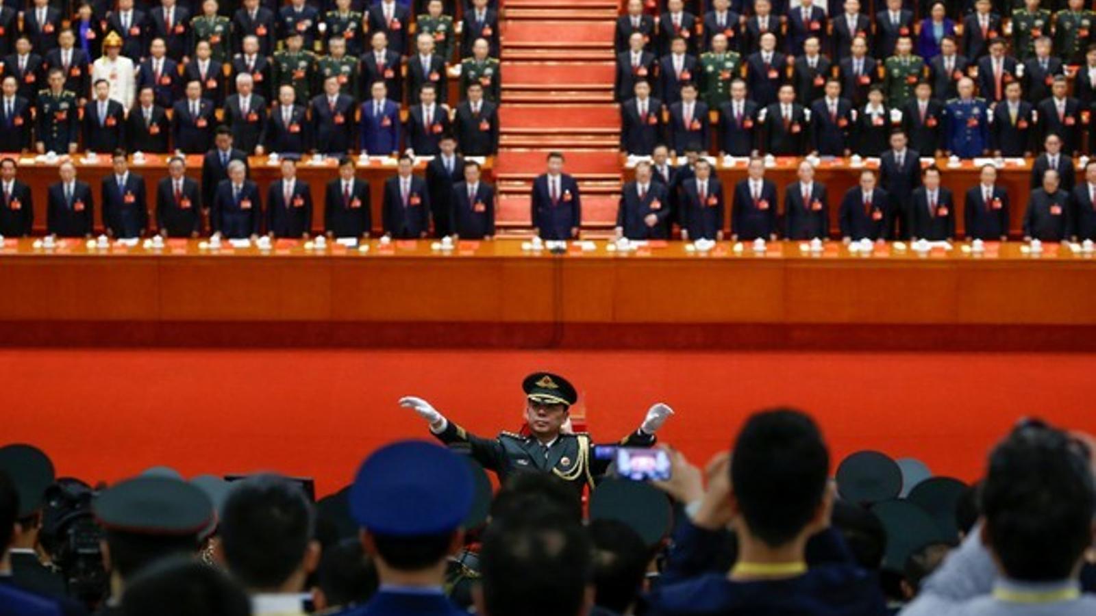 Un militar dirigeix el cor en la cloenda del Partit Comunista, amb Xi Jinping al centre, en la taula presidencial.