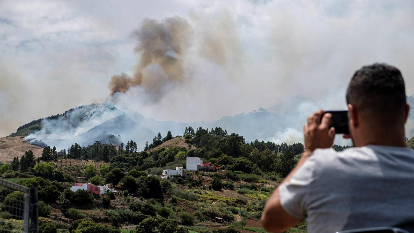 Un home fotografia l'incendi de Gran Canària