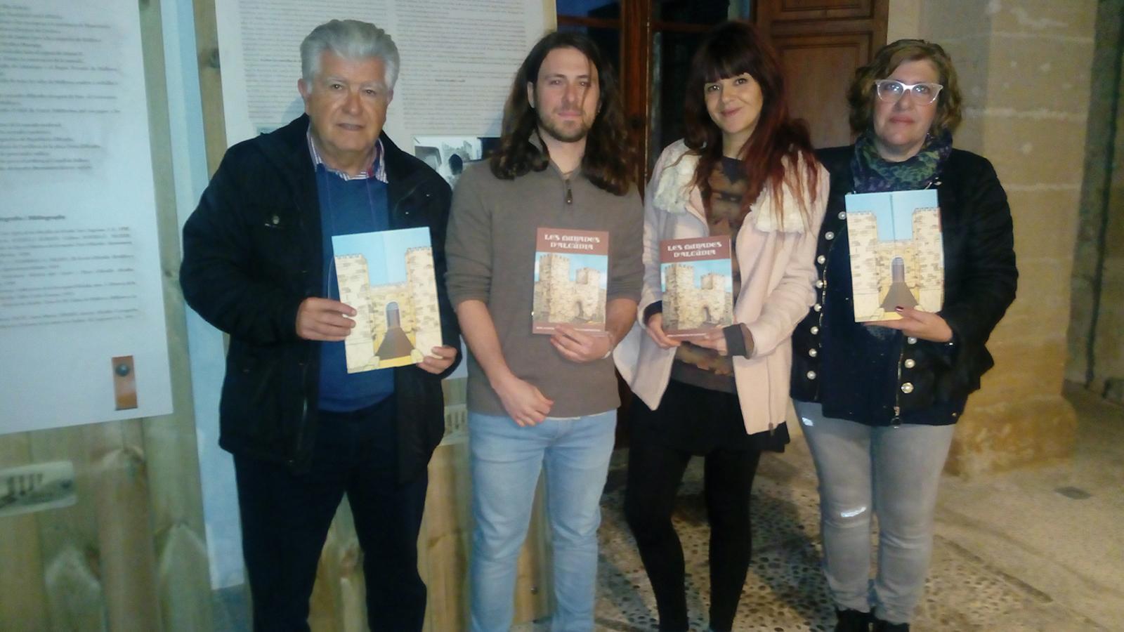 El batle, els autors del treball i la regidora de Cultura i Patrimoni, amb la guia sobre les fortificacions.